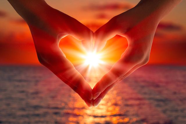 hand in shape of heart framing sunset